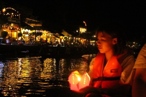 Setting lanterns adrift as we float along the Thu Bon River