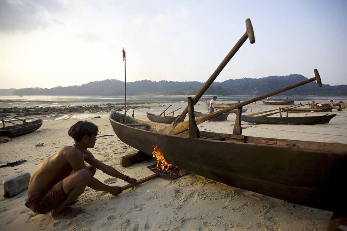 A Moken man works on his dugout canoe