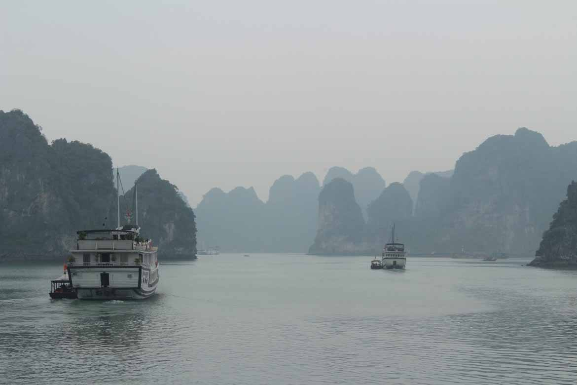 Boats disappear into the mist on Halong Bay