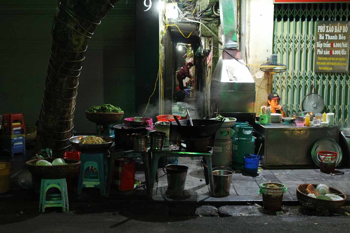 Steam from delicious street food snacks fills the street