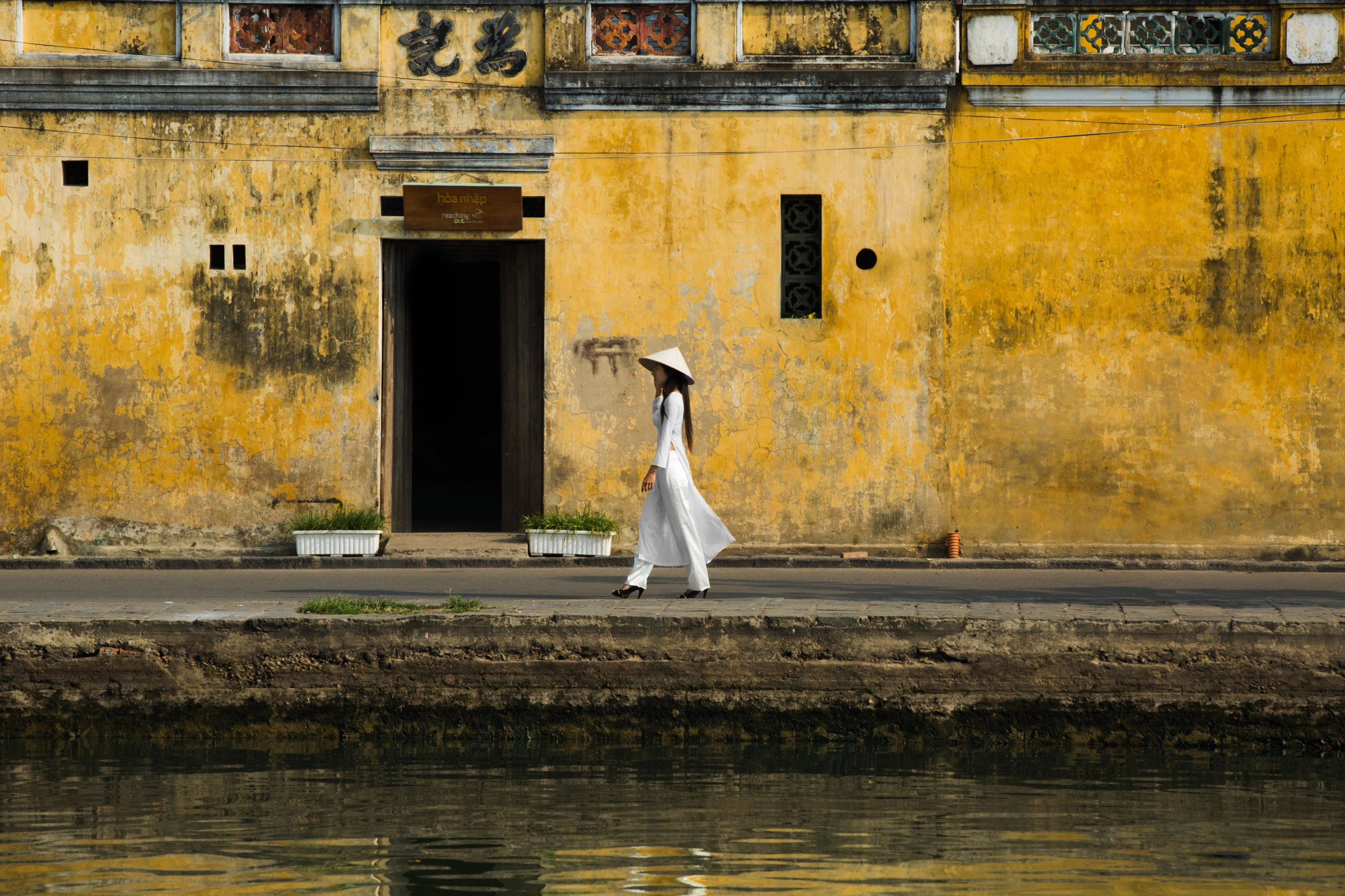 hoi an yellow wall woman walking vietnam